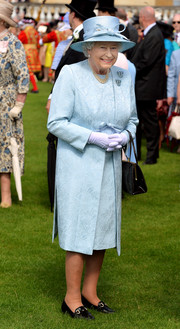 Queen Elizabeth II donned a pastel-blue coat and dress set for a Buckingham Palace garden party.