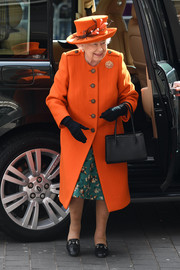Queen Elizabeth II visited the Science Museum wearing a bright orange wool coat.