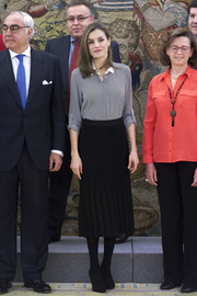 Queen Letizia of Spain paired her shirt with a pleated black skirt by Boss.