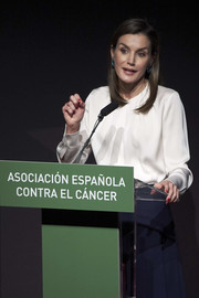 Queen Letizia of Spain kept it minimal in a long-sleeve white blouse by Hugo Boss when she attended a cancer forum in Madrid.
