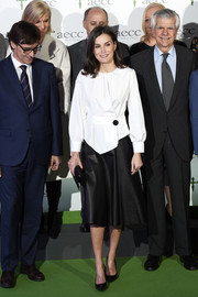 Queen Letizia of Spain attended a forum against cancer wearing a loose white blouse with black button detail.