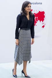 Queen Letizia of Spain paired a black V-neck blouse with a gray plaid skirt for the International Friendship Award.