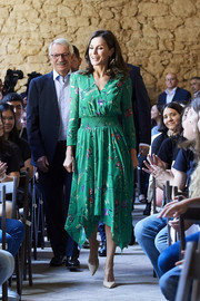 Queen Letizia of Spain looked breezy in a green floral dress by Maje, featuring a crossover bodice and a handkerchief hem, while attending a musical school summer courses opening.