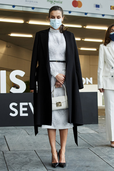 Queen Letizia of Spain layered a black coat by Carolina Herrera over a monochrome print dress for the Tourism Innovation Summit 2020.