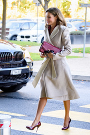 Queen Letizia of Spain headed to a meeting at the WHO headquarters in Geneva wearing a cream-colored wool coat by Carolina Herrera.