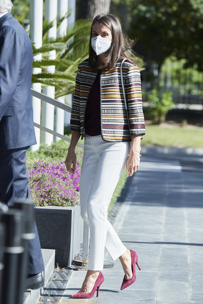 Queen Letizia of Spain teamed burgundy suede pumps with white trousers and a graphic jacket for her visit to Mutua Madrileña Headquarters.
