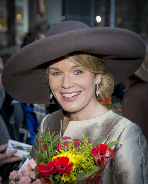 Queen Mathilde of Belgium Dangling Diamond Earrings [day one,lady,facial expression,hat,smile,beauty,floristry,fashion accessory,flower,headgear,fashion,mathilde of belgium,philippe of belgium,wellwishers,bakke grond,holland,culture house,amsterdam,flemish,visit]