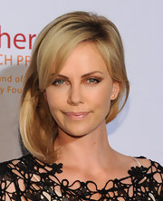 Charlize Theron attended an event for the Africa Outreach Project with her blond locks looking smooth and shiny with lots of movement. She also added a touch of volume through the crown.