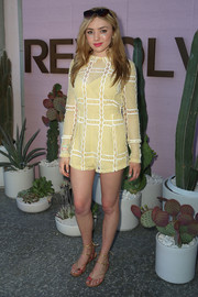 Peyton List paired her romper with strappy gold thong sandals.