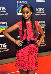 Sara Nuru posed in her ruffled pink cocktail dress. She paired this hot pink number with a black belt and black box clutch.