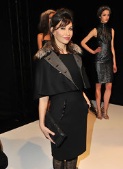 Gina Gershon teamed a black crocodile clutch with a fur-collared skirt suit for a fierce look during the Rafael Cennamo fashion show.