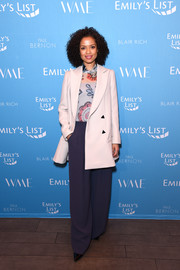 Gugu Mbatha-Raw layered a white blazer over a print blouse for the Raising Our Voices event.