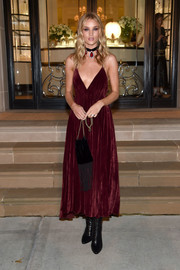 Rosie Huntington-Whiteley put on a daring display in a plunging burgundy velvet dress by Ralph Lauren while attending the label's fashion show.