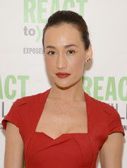 Maggie Q accessorized with a delicate gold cross pendant.