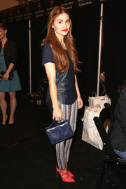 Holland Roden kept it casual and simple at the Rebecca Minkoff fashion show with this blue leather purse, shirt, and print pants combo.