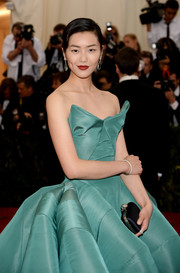 Liu Wen paired a black satin clutch with a strapless ball gown for the Met Gala.
