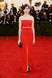 Anne Hathaway was all about sleek minimalism in a red Calvin Klein strapless dress with a midriff peekaboo and a front slit during the Met Gala.