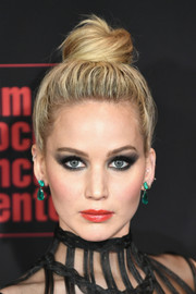 Jennifer Lawrence went bold with her beauty look, pairing her heavy eye makeup with a glossy red lip.