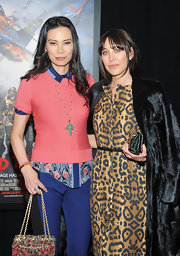 Wendi Deng wore a long chain necklace with a large green cross pendant at the premiere of 'Red Tails'.
