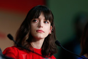Stacy Martin attended the 'Redoubtable' press conference at the Cannes Film Festival wearing her hair in shoulder-length waves with parted bangs.