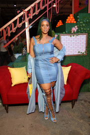 Dascha Polanco matched her dress with thigh-high denim lace-up boots.