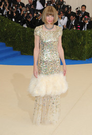 Anna Wintour made a regal entrance at the 2017 Met Gala in a gold Chanel Couture gown that was embellished with gold sequins and a cloud of feathers.