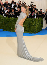 Gisele Bundchen ravished in a slinky silver Stella McCartney gown with an open back during the 2017 Met Gala.