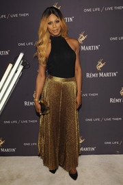 Laverne Cox glammed up her simple top with a pleated gold maxi skirt by Alice + Olivia.