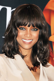 Tyra Banks styled her shoulder length cut into soft waves and softly separated bangs.