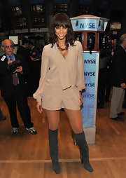 Tyra donned a silk ecru romper with knee-high suede boots for her trip to the NY stock exchange.