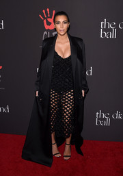 Underneath her voluminous coat, Kim Kardashian was in skin-revealing mode in a black net dress with a bodysuit underlay, also by Balenciaga.
