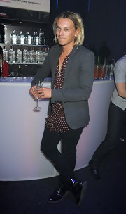 Jamie Campbell Bower layered a gray blazer over a maroon polka-dot shirt for a groovy finish.
