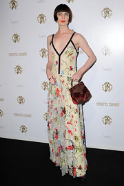 Erin O'Connor accessorized her floral print maxi dress with a top-handle frame bag with maroon and brown leather patchwork.