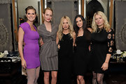 Amanda de Cadenet posed with a group of celebrities wearing a black above-the-knee dress with cutout sleeves.