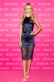 Rosie Huntington-Whiteley was equal parts seductive and elegant in a navy blue Lover dress with a sheer lace hem during the launch of the ModelCo skincare collection.