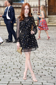 Ellie Bamber topped off her flawless ensemble with a gold clutch.