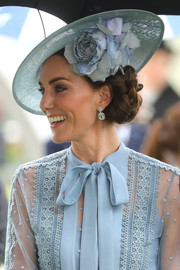 Kate Middleton accessorized with a pastel-blue decorative hat by Philip Treacy to match her blouse.