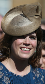 Princess Eugenie accessorized with a sculptural gold hat by Nerida Fraiman at the Royal Society for the Prevention of Accidents Centenary Garden Party.