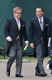 Elton John attended the royal wedding in style wearing gray tailored pants and a black coat. He added a flash of flair with a gold vest and purple tie.