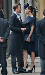 Victoria Beckham completed her flattering dress with a black box clutch.