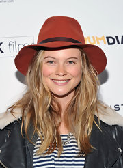 Behati Prinsloo softened her look with a red fedora.