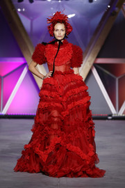 Natasha Poly looked like a glammed-up Little Red Riding Hood in this heavily ruffled gown, complete with a matching headpiece, at the Fashion for Relief runway show.
