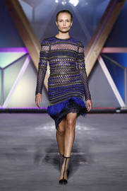 Natasha Poly was tough-glam in a blue mesh dress with a feathered hem at the Fashion for Relief runway show.