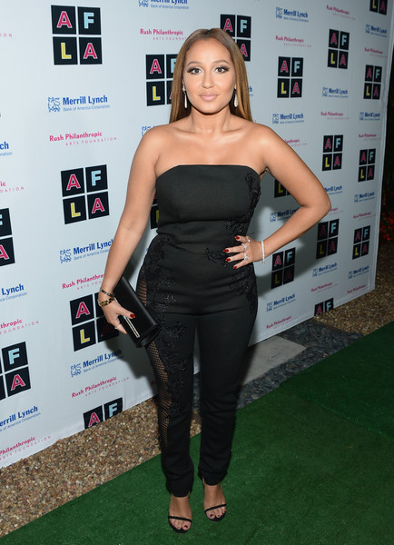 Adrienne Bailon complemented her outfit with a classic black satin clutch.