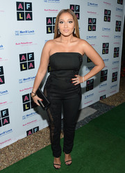 Adrienne Bailon mesmerized in a strapless black Lexi Clothing jumpsuit with see-through mesh panels during the Art for Life Los Angeles event.