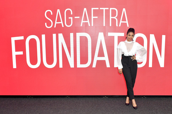 Regina Hall paired her blouse with high-waisted trousers.