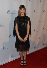 Lizzy Caplan went for vintage glamour in a beaded, caped LBD by Reem Acra at the Saban Community Clinic dinner gala.