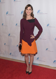 Lizzy Caplan completed her color-block ensemble with the Roland Mouret Belum skirt, in bright orange.