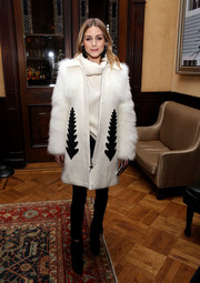 Olivia Palermo went for a luxe cold-weather look in a white Moncler wool coat with fur sleeves and black accents during the Sachin & Babi fashion show.