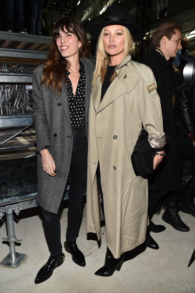 Kate Moss attended the Saint Laurent fashion show looking tough in an oversized beige trenchcoat.